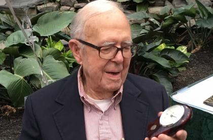 The Rev. Aaron Manderbach '37 opens a gift of a desk clock on the occasion of his 105th birthday.